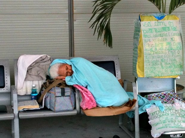 Isaura Lima no momento em que dormia, na manhã de sexta (16), na área externa do Aeroporto Internacional Eduardo Gomes (Foto: Patrick Mota/Rádio Amazonas FM)