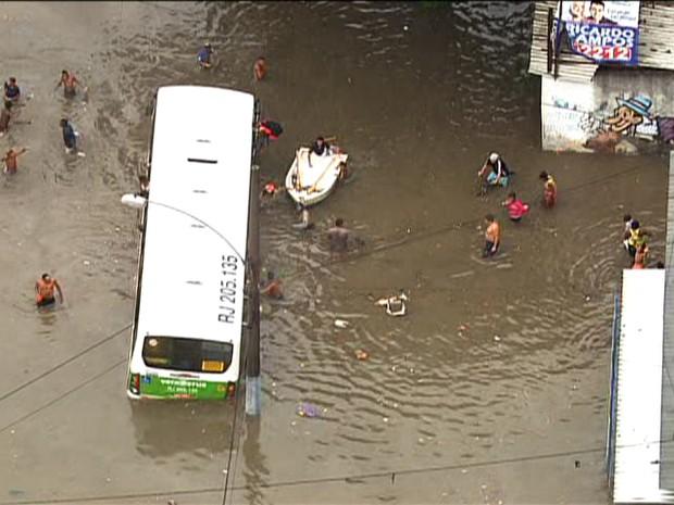 Barco do Corpo de Bombeiros se aproxima de um ônibus enguiçado na Estrada do Quitungo, em Brás de Pina, no Subúrbio. Passageiros pediram socorro no teto do veículo (Foto: Reprodução/TV Globo)