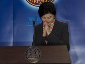 A ex-primeira-ministra da Tailândia, Yingluck Shinawatra, faz gesto tradicional tailandês durante entrevista após sua cassação nesta quarta-feira (7) (Foto: Sakchai Lalit/AP)