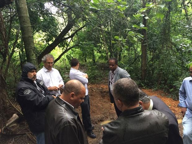 Policiais e representantes do Ministério Público, Defensoria Pública e Condepe observam covas em cemitério clandestino onde estavam corpos (Foto: Kleber Tomaz / G1)