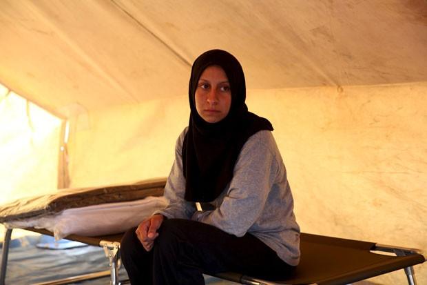 Mulher resgatada após naufrágio pelo Chipre aguarda em centro de refugiados em Kokkinotrimithia nesta quarta-feira (4) (Foto: Yiannis Kourtoglou/Reuters)