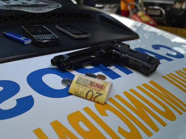Arma de brinquedo, celulares e dinheiro que foram apreendidos.  (Foto: Letícia Bucker/ G1)