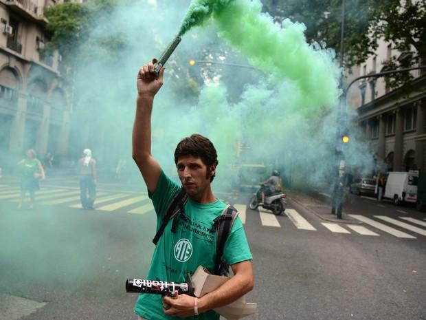 Manifestante protesta nesta terça-feira (29) contra revisão dos contratos de funcionários públicos em frente ao Ministério da Trabalho, em Buenos Aires (Foto: AFP PHOTO/EITAN ABRAMOVICH)