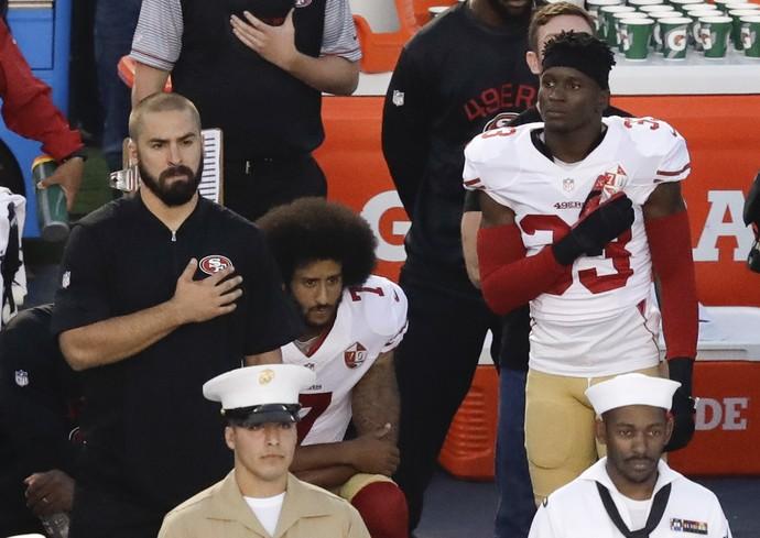 Colin Kaepernick se ajoelha durante a execução do hino nacional (Foto: AP)