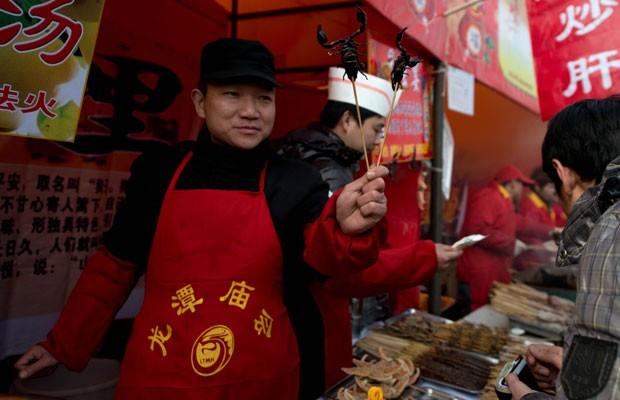 Vendedor ambulante oferece escorpiões no espeto em feira do parque Longtan, em Pequim, nesta quarta-feira (13). O ano novo lunar da cobra é comemorado por mais de 1 bilhão de asiáticos em semana de festividades. (Foto: Ed Jones/AFP Photo)