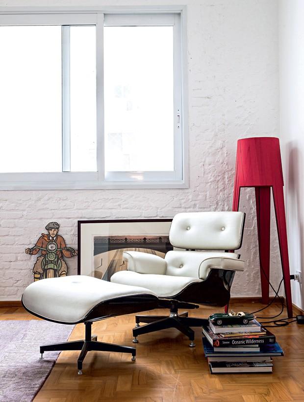 Em um canto, a espreguiçadeira criada pelos norte-americanos Ray e Charles Eames, em 1956, fica junto da luminária Dress, design de Jehs & Laub para Fambuena. Livros da Livraria Cultura (Foto: Lufe Gomes/Editora Globo)