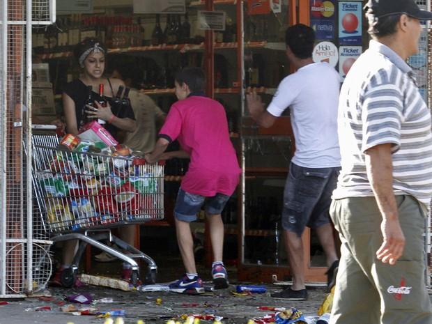 Pessoas saqueiam mercado em Córdoba na Argentina durante protesto de policiais (Foto: AFP)