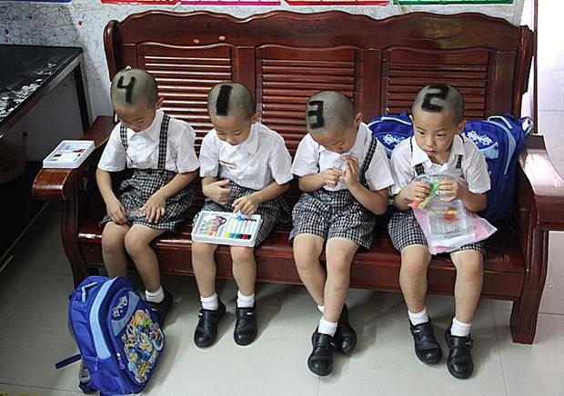 uadrigêmeos chineses exibiram um corte de cabelo estilizado ao serem fotografados em Shenzhen (Foto: AFP)