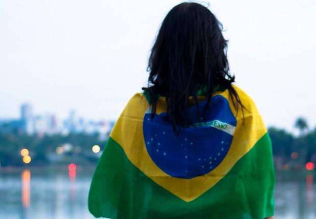 Mulher enrolada na bandeira do Brasil (Foto: Reprodução/Facebook)