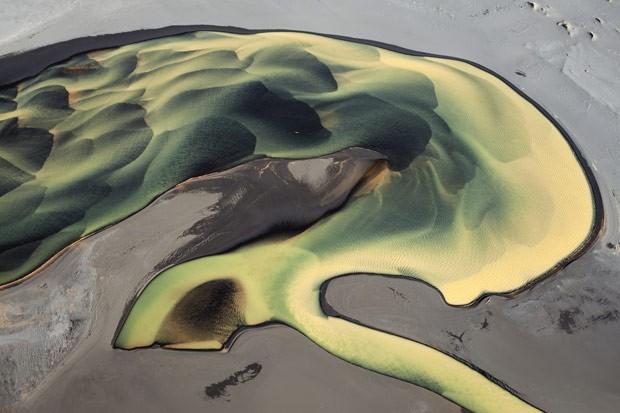 Rio sinuoso cruza a praia de areias cinzas de Landeyjarsandur (Foto: Haarberg Photography/Barcroft Media)