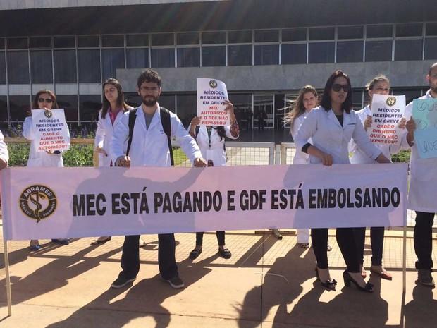 Médicos residentes da rede pública do DF seguram cartazes em protesto para cobrar repasse de aumento nas bolsas dado pelo MEC (Foto: Mateus Vidigal/G1)