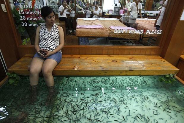 Mulher coloca os pés em tanque com peixes que fazem o trabalho de pedicure (Foto: Akhtar Soomro/Reuters)