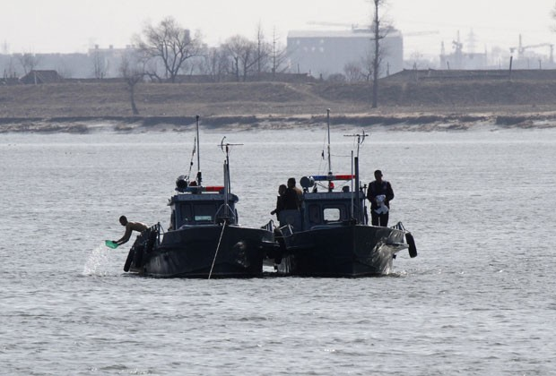 Militares norte-coreanos são vistos em barcos de patrulha perto da fronteira com a China (Foto: Jacky Chen/Reuters)