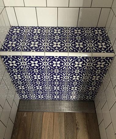 No box do chuveiro, nos dois banheiros, André incluiu um banco em alvenaria. Para captação da água, utilizou grelhas de inox Alezzia - Palmetal (Foto: Divulgação/André de Freitas)