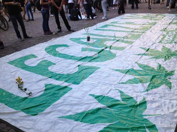 Cartaz estendido no chão divulga mensagem sobre a maconha  (Foto: Pamela Kometani/ G1)