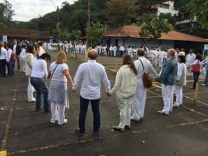 Cerca de 150 pessoas que estão na fila para ver o velório dão as mãos e fazem uma oração pelo médium Gilberto Arruda (Foto: Cristina Boeckel / G1)