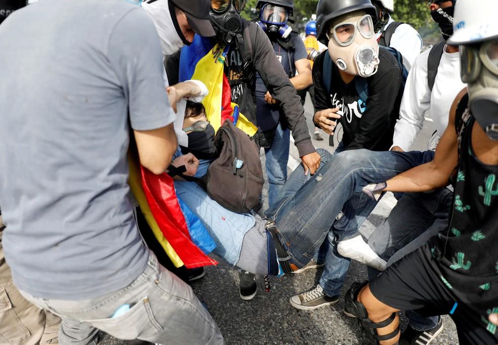 Jovem baleado pelas forças de segurança da Venezuela é socorrido por manifestantes durante protesto em Caracas, na quinta-feira
