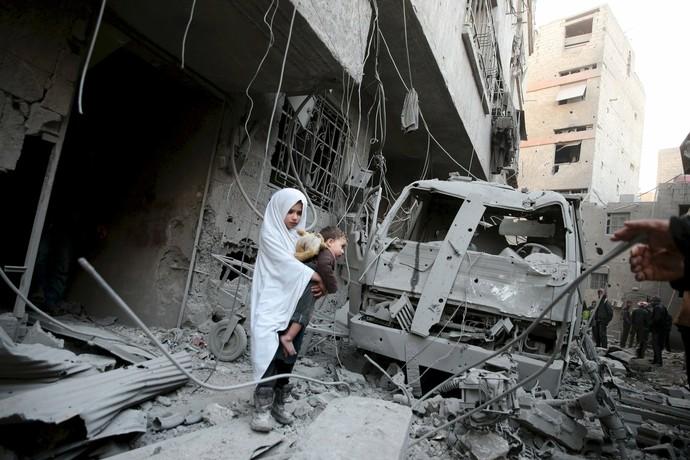 Criança com a sua boneca em cidade completamente destruída na Síria (Foto: Reuters)