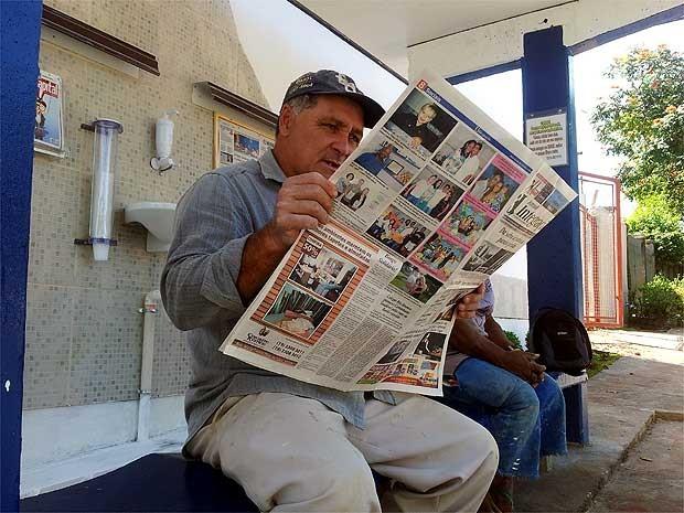 Os pedreiros Gentil Ferreira lendo jornal  no ponto de ônibus vip (Foto: Luciano Calafiori/G1)