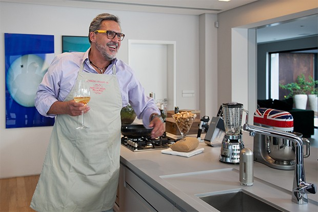 Na cozinha gourmet ele se delicia com uma taça de vinho branco (Foto: Marcos Rosa/  Ed. Globo)