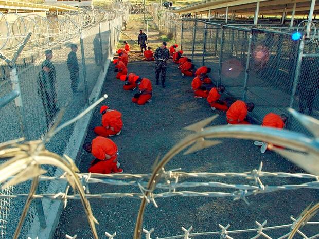 Detentos são vigiados por miliares dos EUA no campo temporário X-Ray, que depois foi fechado e substituído pelo Campo Delta, na prisão de Guantánamo, em foto de 11 de janeiro de 2002 (Foto: Reuters/U.S. Department of Defense/Petty Officer 1st Class Shane T. McCoy/Handout/Files via Reuters)