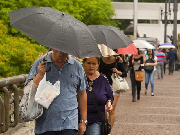 Pedestres se protegem da chuva na manhã desta terça-feira no Viaduto do Chá, no Centro de SP (Foto: Gabriel Soares/Brazil Photo Press/Estadão Conteúdo )