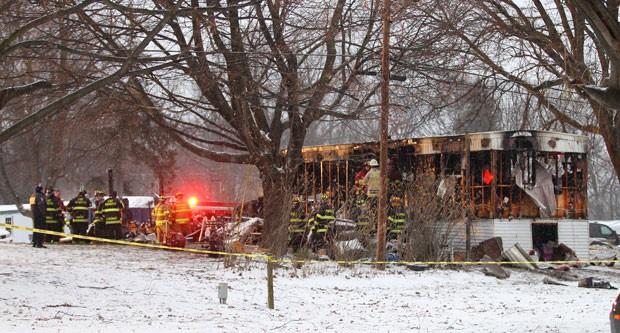 Bombeiros trabalham no trailer que pegou fogo em Penfiel, Nova York, na segunda-feira (20). Um menino de 8 anos morreu após salvar seis parentes do incêndio (Foto: Rochester Democrat and Chronicle, Jamie Germano/AP)
