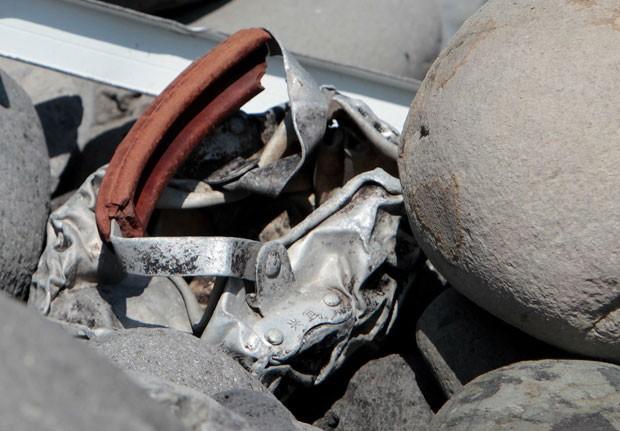 Foto deste domingo (2) mostra pedaços metálicos achados na Ilha de Reunião; autoridade malaia descartou que eles sejam de avião da Malaysia Airlines (Foto: Richard Bouhet/AFP)