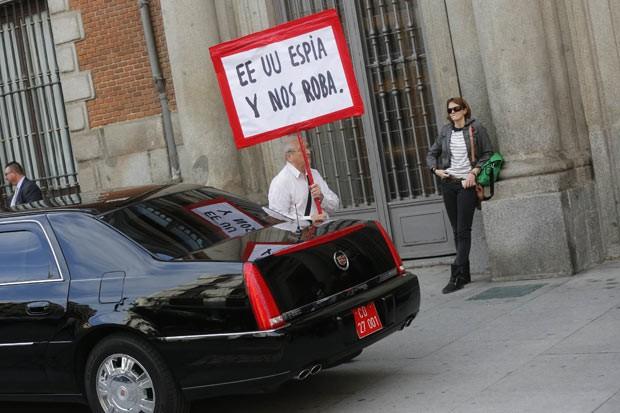 Homem segura cartaz em protesto contra os EUA nesta segunda-feira (28) em frente ao prédio do ministério de Relações Exteriores, em Madri (Foto: AFP)