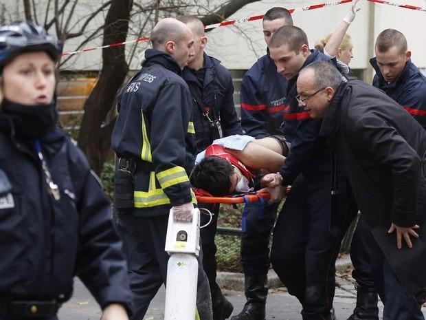 Bombeiros levam vítima em maca após ataque a jornal satírico em Paris (Foto: Jacky Naegelen/Reuters)