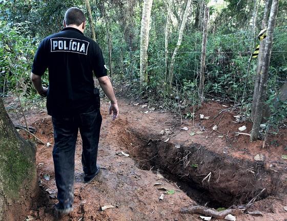 Policial observa cova encontrada no começo de fevereiro no Parque das cerejeiras em São Paulo (Foto: MARCIO FERNANDES/ESTADÃO CONTEÚDO)