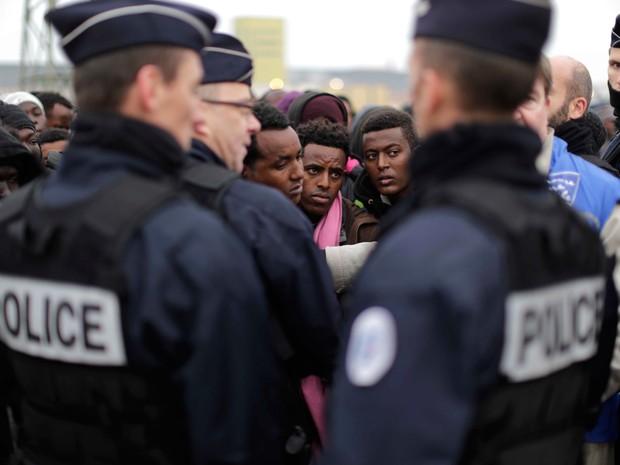 Policiais organizam fila para a transferência de migrantes acampados em Calais na manhã desta segunda-feira (24) (Foto: Emilio Morenatti/ AP)
