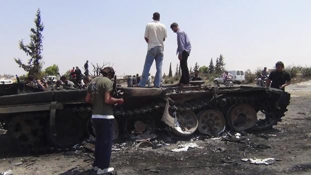 Membros do Exército de Libertação da Líbia observam destroços de tanque em Jerjenaz, em imagem do último dia 29 (Foto: Reuters)