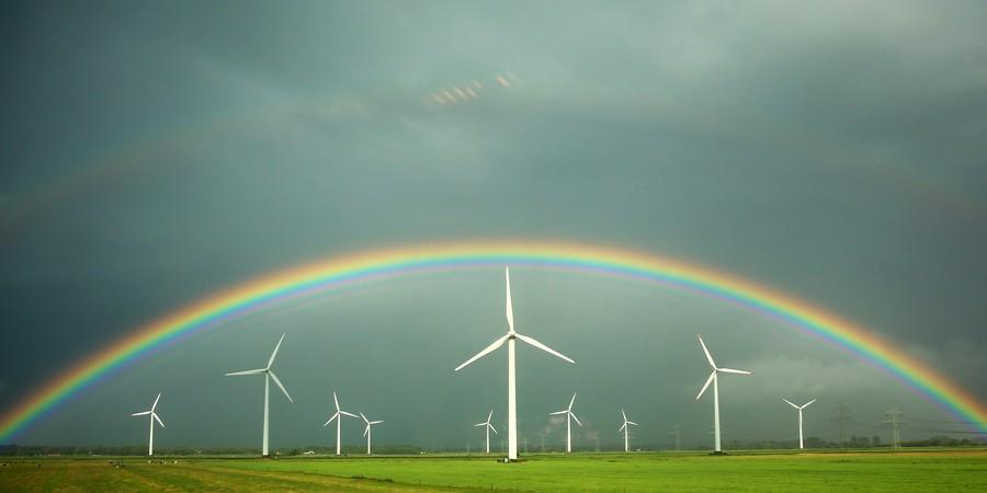 Imagem feita pela janela de um trem registra arco-íris no meio de campo de energia eólica em Wilster, na Alemanha (Foto: AP Photo/dpa, Christian Charisius)