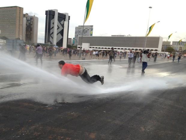 Manifestante cai ao ser atingido por jato d'água em Brasília (Foto: Felipe Neri/G1)