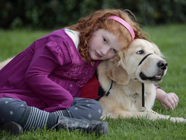 Alyssa Howes, de 11 anos, abraçada ao cão Flint, que é seu fiel escudeiro e vigilante noturno (Foto: Damian Dovarganes/AP)