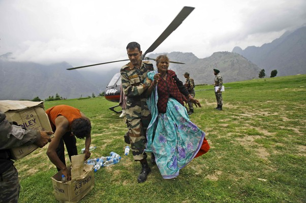 Equipe de resgate socorre uma senhora que estava presa no alto de uma montanha em Joshimath, na Índia. Cerca de 22 helicópteros trabalham para regatar as vítimas das chuvas de monção, que já mataram mais de mil pessoas no norte do país (Foto: AP Photo/Rafiq Maqbool)