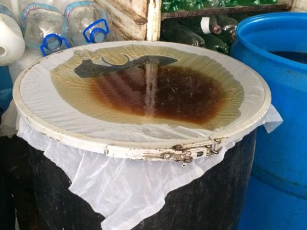 Óleo precisa ser peneirado antes de ser utilizado na fabricação dos produtos de limpeza (Foto: Michelle Farias/G1)