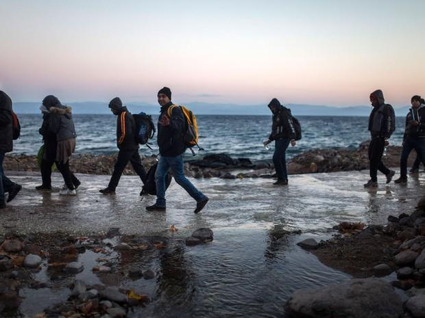 Refugiados afegãos vindos da costa da Turquia caminham em praia da ilha grega de Lesbos, na segunda (30) (Foto: AP Photo/Santi Palacios)