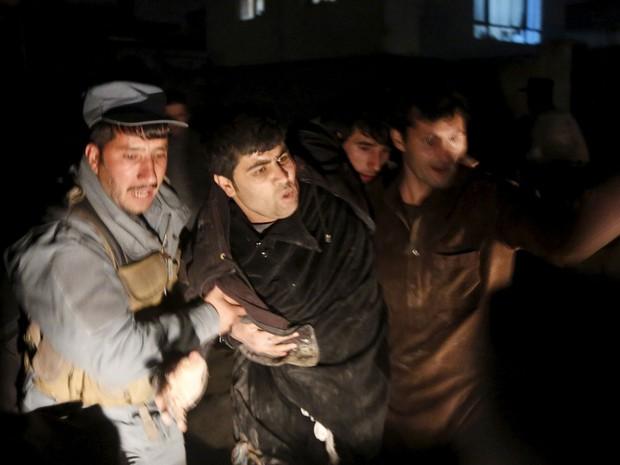 Policiais afegãos socorrem homem ferido em explosão em Cabul causada por carro-bomba (Foto: Omar Sobhani/Reuters)