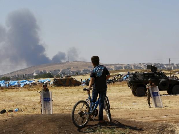 Menino observa fumaça saindo de Kobane, do outro lado da fronteira com a Turquia (Foto: REUTERS/Murad Sezer)