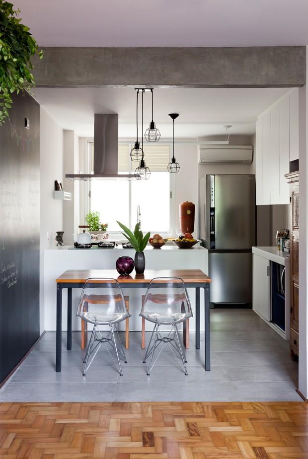O piso de porcelanato de concreto foi escolhido pela praticidade de manutenção e limpeza; e para demarcar visualmente a separação de sala e cozinha.  Mesa e cadeiras Base Metálica da Tok&Stok. Pendentes Oppa e Reka (Foto: Maira Acayaba)