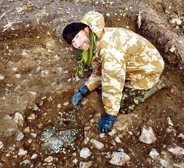 Laurence Egerton, de 51 anos, posa com as moedas romanas que descobriu na Inglaterra (Foto: Reprodução/Twitter/British Museum)