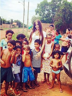 Neyla Rodrigues com algumas crianças que moram no setor Jardim Taquari (Foto: Reprodução/Facebook)