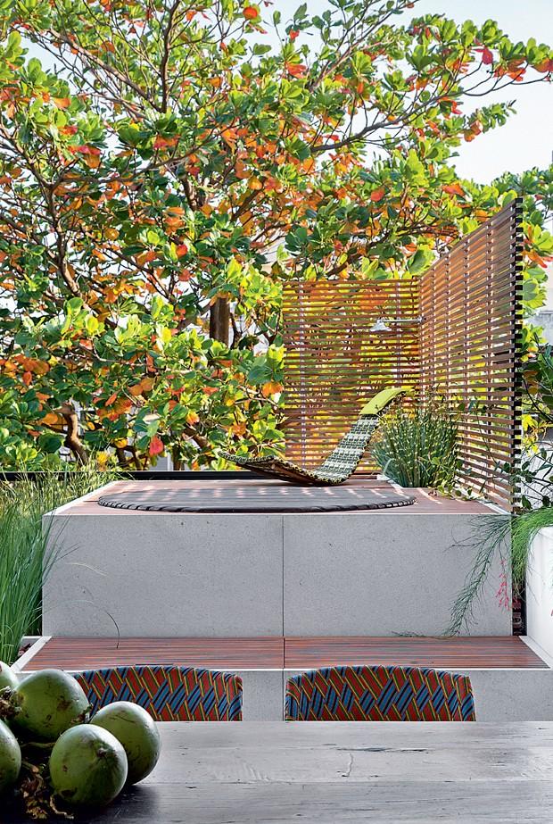 Ofurô. A banheira fica instalada em um canto do terraço, junto a um deque de cumaru. Um painel ripado dá mais privacidade ao local. Poltrona da Dedon, na Collectania (Foto: Denilson Machado / MCA Estúdio / Divulgação)
