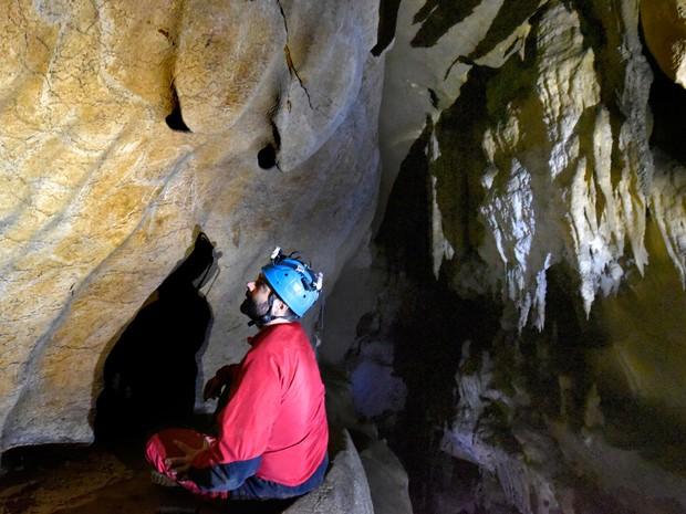 Em foto não datada, o arqueólogo Diego Garate observa pinturas encontradas na caverna Atxurra, na Espanha, e que teriam mais de 12 mil anos (Foto: HO/AFP)