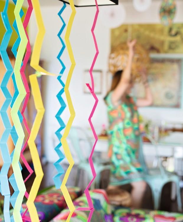 Tiras de papel-cartão em ziguezague, penduradas no lustre, imitam serpentinas (Foto: Elisa Correa / Editora Globo)