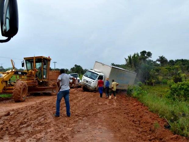 Pessoas tentar retirar caminhão que atolou na estrada de terra (Foto: Dayanee Saldanha/G1)