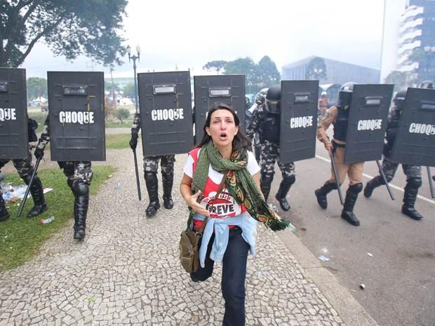 Mulher corre de paredão da Tropa de Choque durante repressão do protesto de professores em Curitiba (PR) (Foto: Daniel Castellano/Agência Gazeta do Povo)
