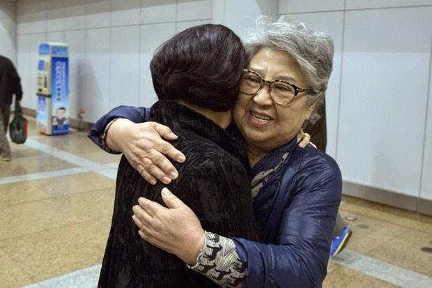 Sandra Suh abraça outra mulher ao chegar ao aeroporto de Pequim nesta quinta-feira (9) após ser deportada pela Coreia do Norte (Foto: Ng Han Guan/AP)